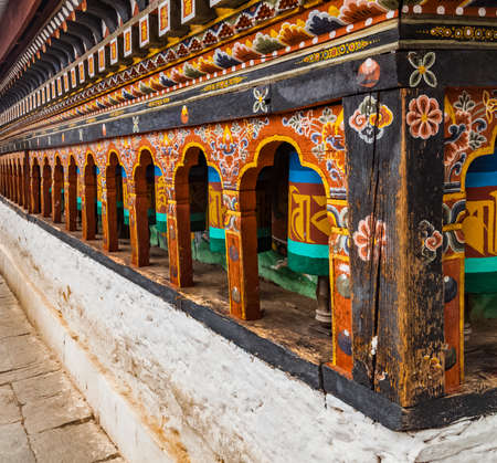 Row of painted turning prayer wheels mantra in Bhutan with traditional writing mantra which sounds as
