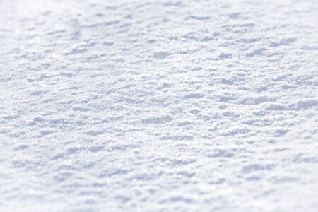 Background of sparkling fresh white snow texture with light blue sky reflection tone.