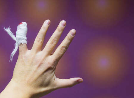 Close-up? a female hand with injured bleeding finger with bloody gauze on it.