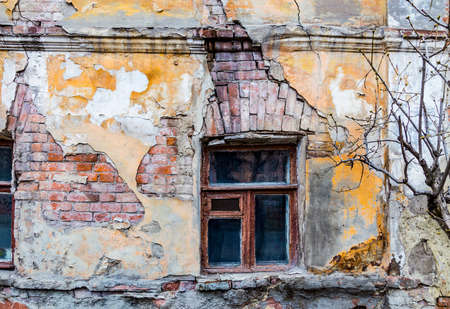 Old vintage brick house with cracks and old wooden window