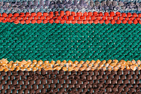 Close up of a colorful handmade motley striped rug or carpet of different colors - red, green, yellow and brown.