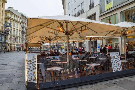 Vienna, Austria - October 2019: Outdoor electric heating infrared lamps under umbrella in street cafe in cold autumn season Stock fotó