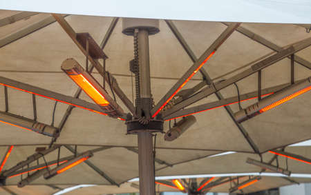 Outdoor electric heating infrared lamps under umbrella in street cafe in cold season (winter, autumn or spring)