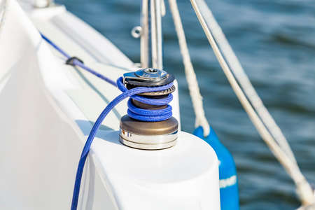 Sailing boat yacht sheet winch with blue rope closeup