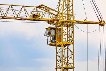 Partial view of a yellow tower construction crane - Operating cabin with operator inside it.