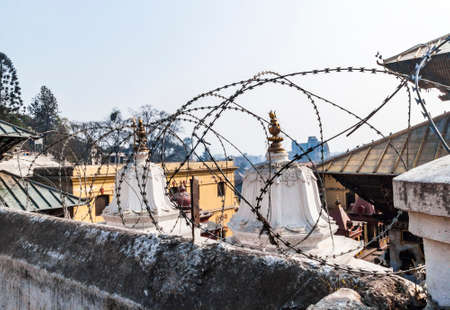 Barbed wire around of Pashupatinath complex, cremation of the dead on the banks of the sacred Bagmati river, partially destroyed during the earthquake 2015. Kathmandu, Nepal. Selective focus on wire. Stock Photo