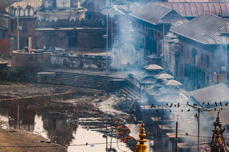 Pashupatinath complex, cremation of the dead on the banks of the sacred Bagmati river, partially destroyed during the earthquake 2015. Smoke because of funeral pile. Kathmandu, Nepal