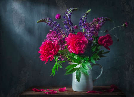 Classic still life with beautiful purple peony and lupine flowers bouquet in white jug. Art photography.