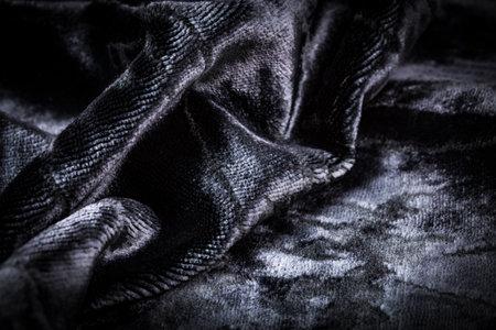 Abstract black creasy velvet fabric background texture