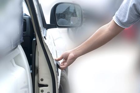 cerrar la puerta: Primer plano de un hombre de la apertura de una puerta de un coche en un garaje Foto de archivo
