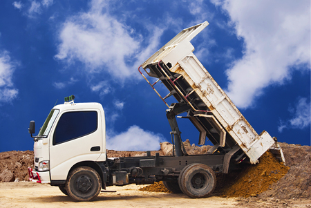 Dumper truck unloading soil or sand at construction site during road works at blue sky background Stock Photo - 50984344