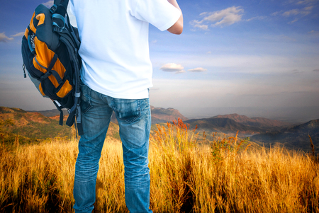 Man Traveler with Backpack looking at mountain landscape on sky background