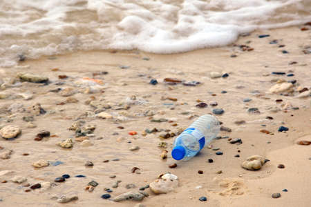 Environmental pollution: plastic bottle on the beach.