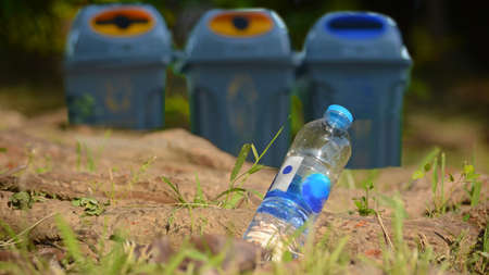 A bottle of drinking water littering on a road ground floor at the green park with blurred a trash bin in the sideway for an environmental cleaning concep