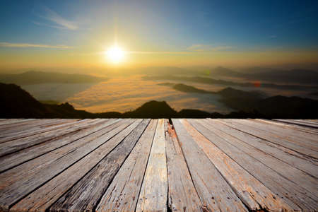 An empty wooden terrace with mountain view and mist during sunrise.