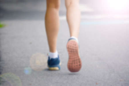 an athletic pair of legs running or jogging on a path during sunrise or sunset - healthy lifestyle concept done with a soft glowing filter blurred out so text can be placed over the image