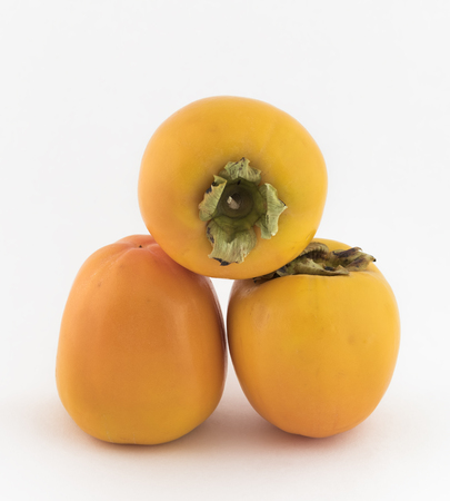 persimmons: Three persimmons with white background