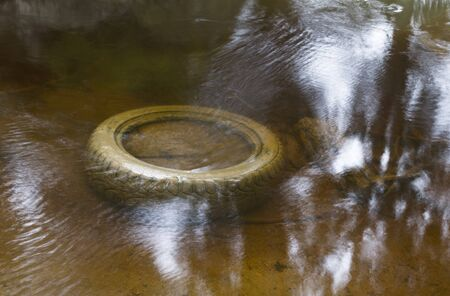 abandoned car: Abandoned car tire in the water Stock Photo