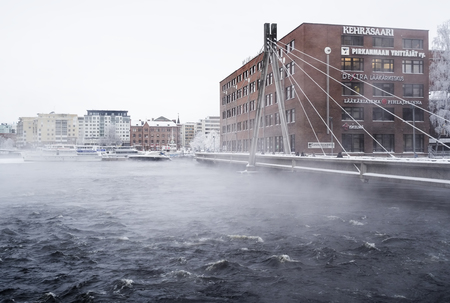 TAMPERE, FINLAND - JAN 2016. Cold and cloudy winter day next to Tammerkoski. Place is called Kehrsaari which is old idyllic mart and industrial centre. Temperature were below -20 degrees. Editorial