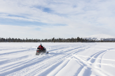 Going with snowmobile towards to mountain in Lapland