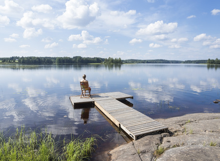 Jeune femme appréciant la chaude journée d'été en Finlande à côté du lac Banque d'images - 62538611