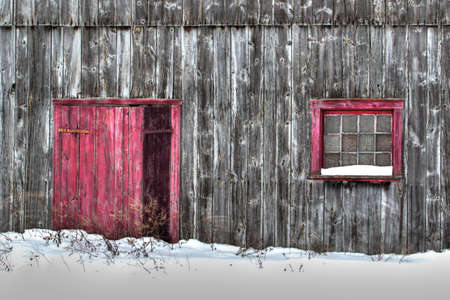 Close up of old gray wood planks barn in a snow field with red door and red window Foto de archivo