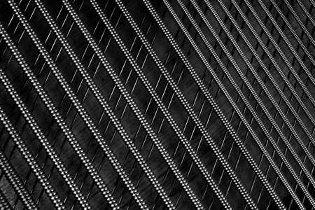 Black and white diagonal crossing piano strings close up