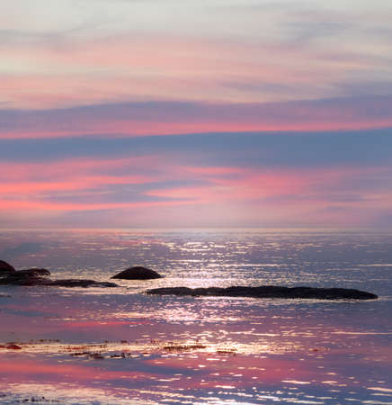 Pink and blue sky reflecting in water soft seascape Stock Photo