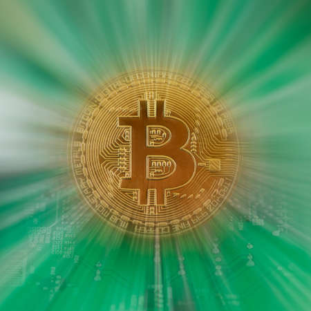 Zooming in on a gold color physical bitcoin crypto currency with green circuit board background