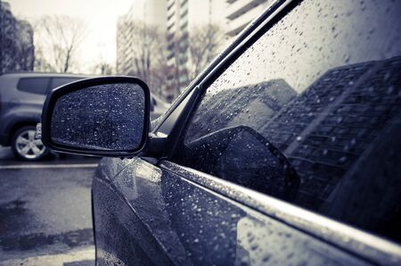 Raindrops on side rearview mirror in rainy day.