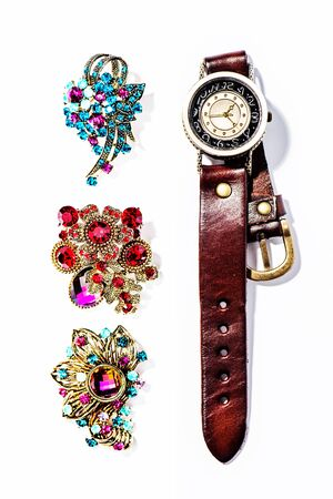 A brooch and a watch on a white background. Archivio Fotografico