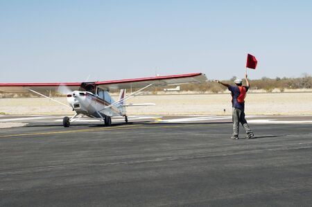 An airshow visitor is directed to the aircraft parking area. photo