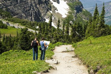 hikers checking the map on Highline Trail in Glacier National Park Stock Photo
