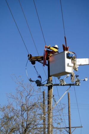 Electric utility lineman working on power lines. Stock Photo