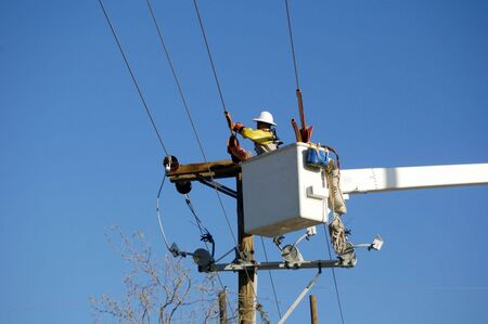 electric utility: Electric utility lineman working on power lines. Stock Photo
