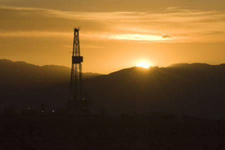 oilfield: oil and gas drilling rig at sunrise in Wyoming