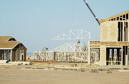 Workers move a roof truss into position on a new house under construction in a new neighborhood.