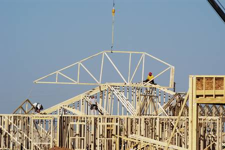Workers move a roof truss into position on a new house under construction in a suburban neighborhood. photo