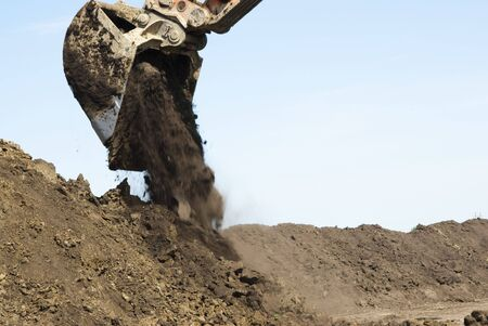 dumping: an excavator dumping a bucket of dirt Stock Photo
