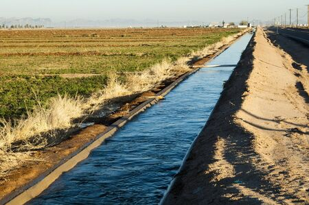 irrigated: water flowing in an irrigation canal in Arizona Stock Photo