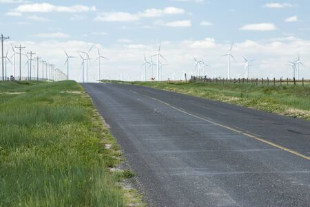 a wind farm on the horizon in Texas with heat waves from the highway photo