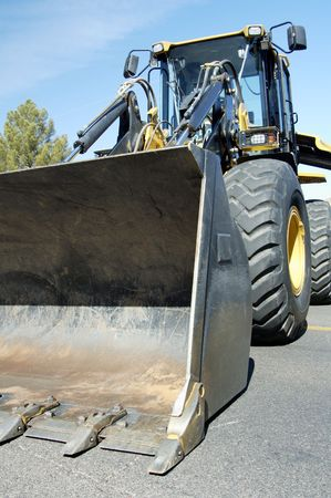 buildingsite: A front end loader staged for a new construction project in a suburban area.