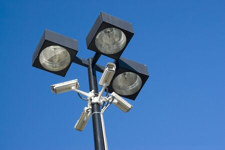 security cameras mounted on floodlights in a parking lot