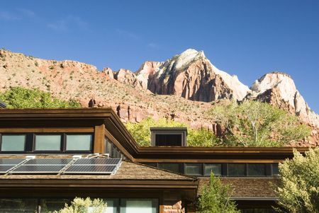 ut: Solar panels attached to the roof of the visitors center in Zion National Park in southwest Utah. Sandstone formations in the background.