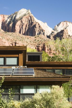 Solar panels attached to the roof of the visitors center in Zion National Park in southwest Utah. Sandstone formations in the background. photo