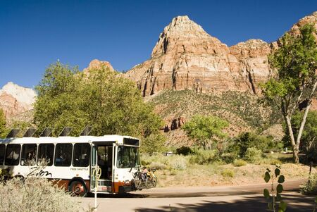 fueled: A porpane fueled shuttle bus stops at the Visitors Center in Zion National Park in southwest Utah. Sandstone formations in the background. Bicycles loaded in the front of the bus