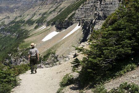 a park ranger walking on Highline Trail in Glacier National Park Reklamní fotografie