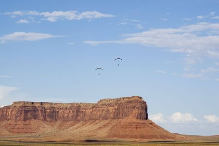 two powered paraglider pilots in flight over Monument Valley