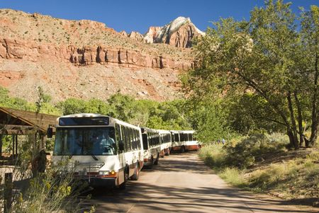 A porpane fueled shuttle bus stops at the Visitors Center in Zion National Park in southwest Utah. Sandstone formations in the background.