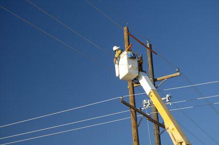 Electric utility lineman working on power lines. Reklamní fotografie